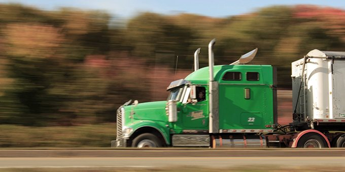 Green big rig on highway
